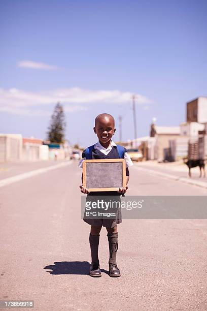 Young School boy standing in township street with chalk board, Cape Town, Western Cape Province, South Africa