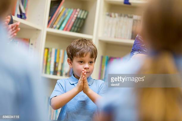 Young School Boy With His Hands Clasped