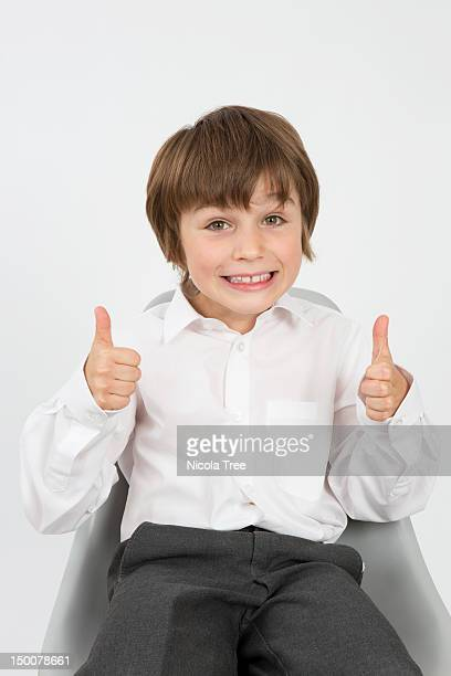 A young school boy with his thumbs up
