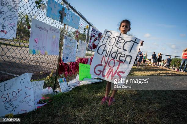 A young school child holds a sign 'Protect Children NOT Guns' at Stoneman Douglas High School On February 14 a former school Stoneman Douglas student...