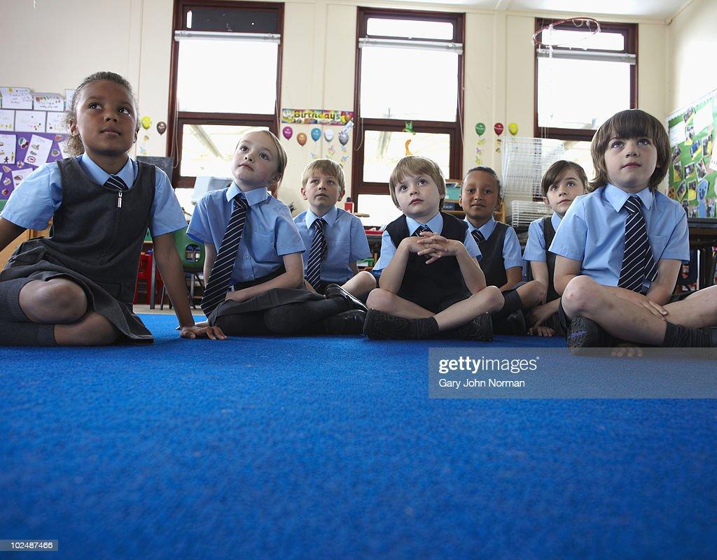 Young school children listen to teacher : Stock Photo