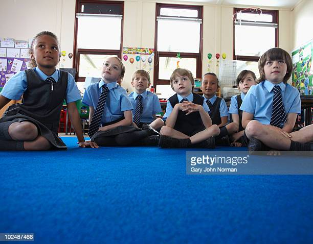 young school children listen to teacher - primary school child stock pictures, royalty-free photos & images