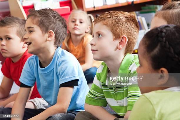 Young School Children escuchar música durante historia tiempo en clase