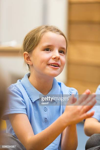 Young School Girl Clapping in the Classroom