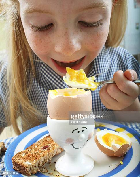Young school girl eating egg for breakfast