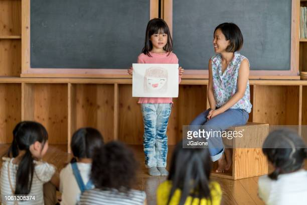Young school girl giving a presentation in class