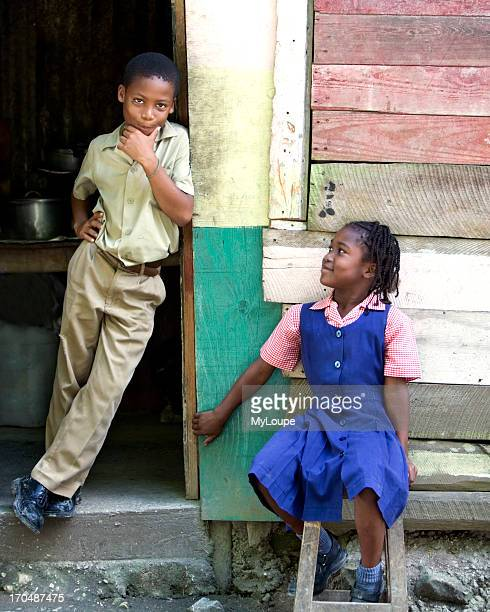 Young school girl in uniform sits on a stool near a boy in uniform leaning against the door of a small lunch shack village of Lette near Montego Bay...
