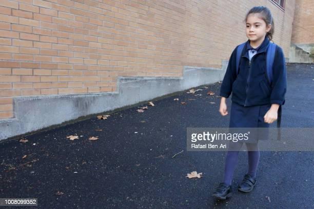 young school girl walking to school - rafael ben ari stock-fotos und bilder
