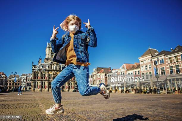 young school girl wearing a face mask in the centre of a dutch city - south holland stock pictures, royalty-free photos & images