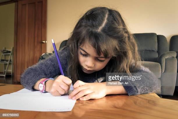 Young school girl writing