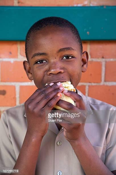 Young schoolboy eating a hotdog, Kwazulu Natal Province, South Africa