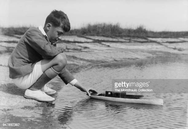 Young schoolboy playing outdoors with a toy boat on a pond England12th August 1931