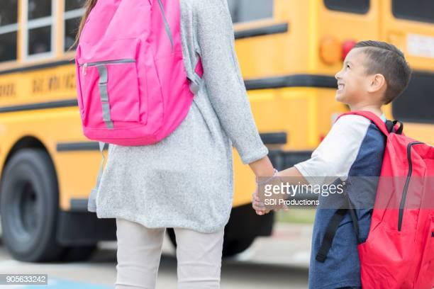 Junge Schüler stützt sich auf ältere Schwester an seinem ersten Tag der Schule