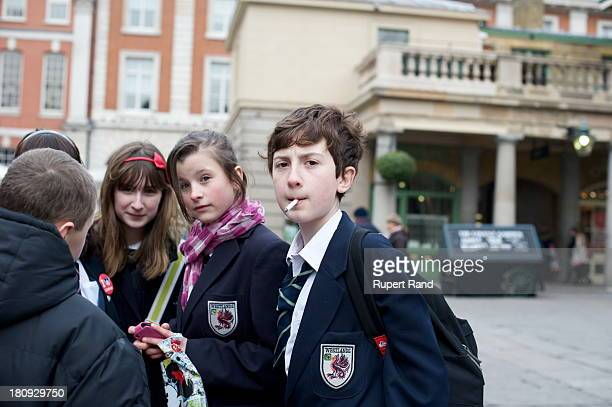 Young schoolboy smokes a cigarette in Covent Garden Piazza, London.