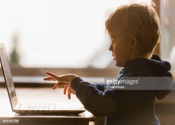 young schoolboy working on laptop computer - sporting term fotografías e imágenes de stock