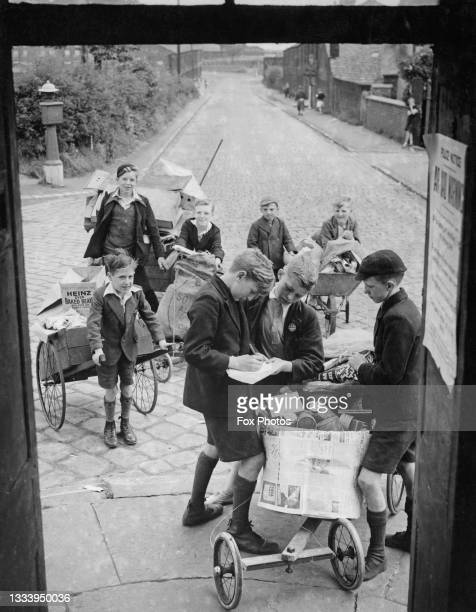 Young schoolboys using hand carts and trolleys collect paper, glass and other scrap metals for the National Salvage Campaign to help recycle...