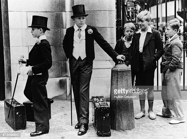 Young schoolboys wearing formal attire arrive at Lords Cricket Ground for a cricket match between Eton and Harrow England