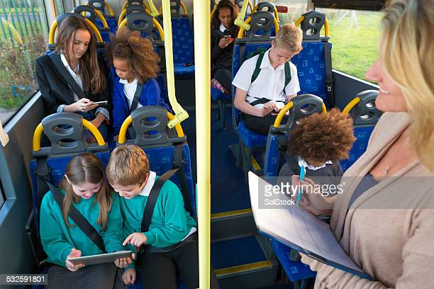young schoolchildren using technology on bus - register stock photos and pictures