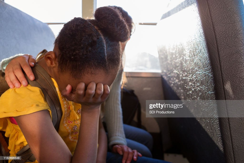 Young schoolgirl cries as her friend consoles her : Stock Photo