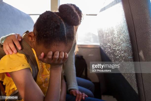 junge schülerin schreit, wie ihre freundin sie tröstet - staatliche schule stock-fotos und bilder