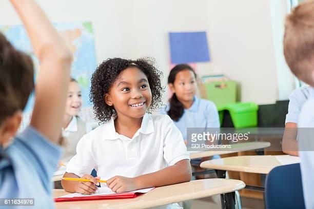 Young schoolgirl listens to teacher in class