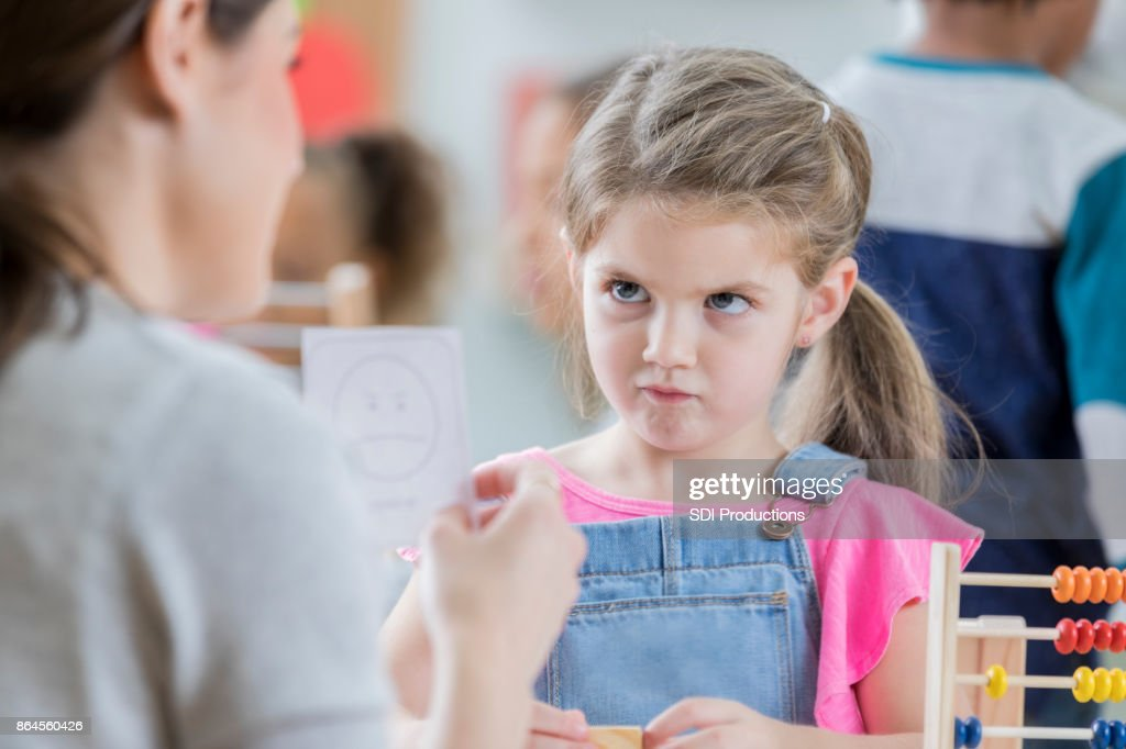 Young schoolgirl mimics face on emotion flash card : Stock Photo