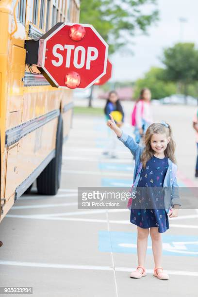 young schoolgirl points to flashing school bus stop sign - public service announcement stock photos and pictures