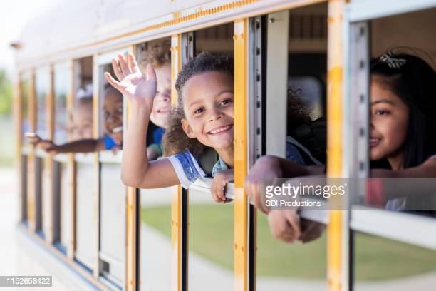 young schoolgirl smiles at camera and waves - state school stock pictures, royalty-free photos & images