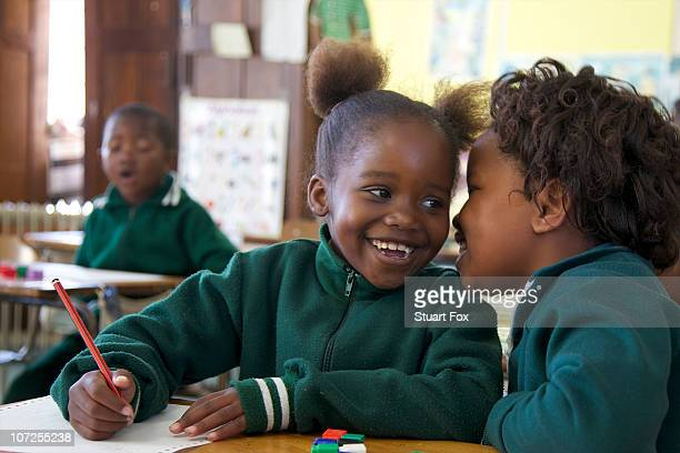 Young schoolgirl whispers to her friend in class, KwaZulu Natal Province, South Africa