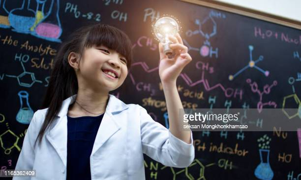 young science students are thinking on the background with light bulbs and science formulas. kids ideas. - very young thai girls stock photos and pictures