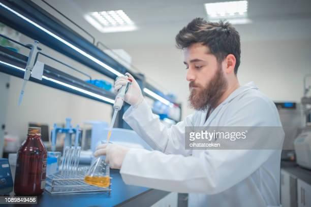 young scientist in his laboratory - químico imagens e fotografias de stock