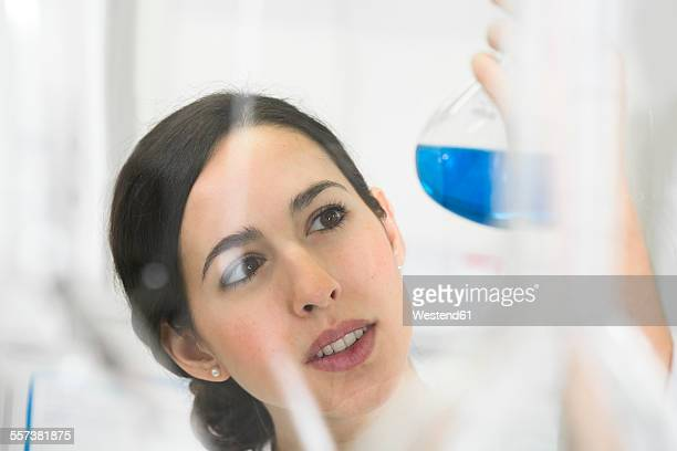 Young scientist in laboratory judging blue liquid in flask