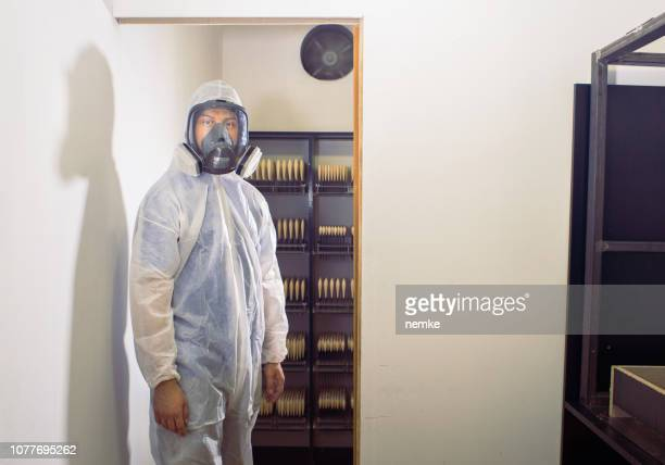 young scientist in protective suit in laboratory or factory - biochemical weapon stock pictures, royalty-free photos & images