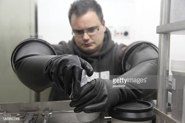 young scientist working in a glove box - physicist stock pictures, royalty-free photos & images