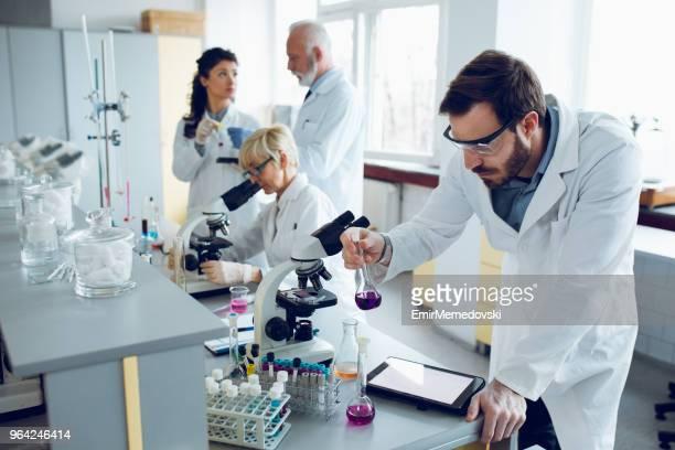 Jeune scientifique travaillant avec des tubes à essai dans un laboratoire