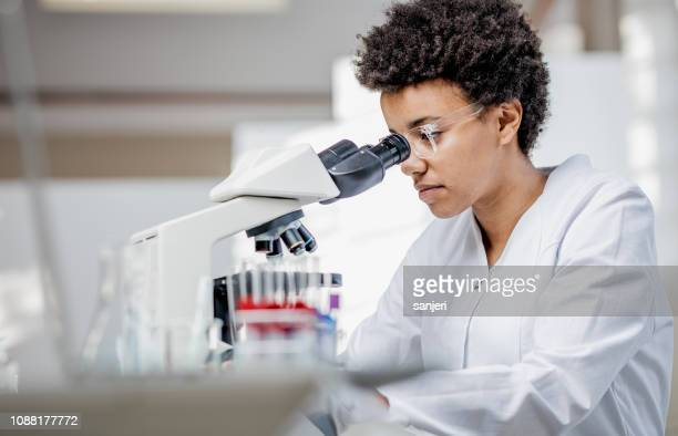 young scientist working with the microscope - cancer illness stock pictures, royalty-free photos & images