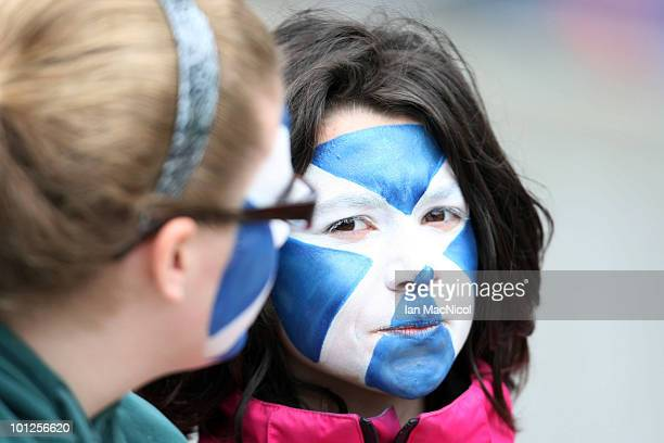 Young Scotlabnd fans with Saltires painted on their faces watch the action during the IRB Edinburgh Sevens Festival at Murrayfield Stadium on May 29...