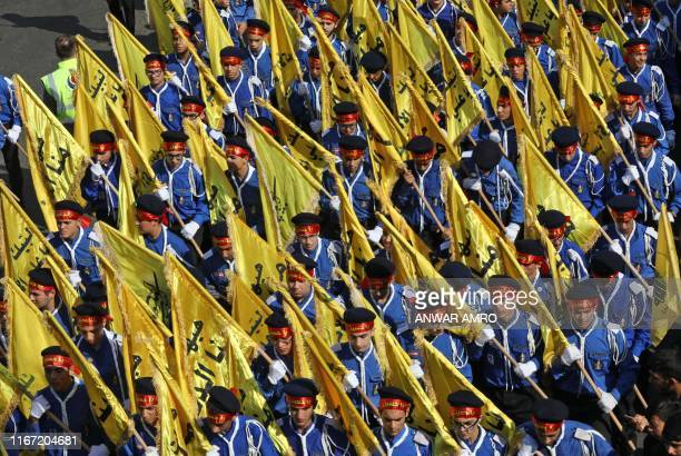 Young scouts from the Lebanese Shiite Hezbollah movement march during a religious mourning procession on the tenth day of the lunar month of...