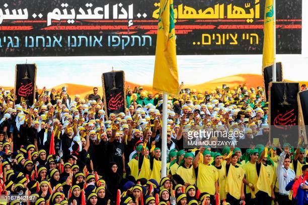Young scouts of the Lebanese Shiite Hezbollah movement take part in a religious procession marking the thirteenth day of the Islamic month of...