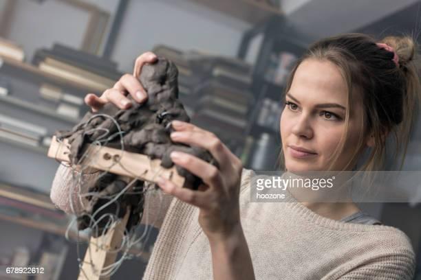junge bildhauer schafft eine tonskulptur - bildhauer stock-fotos und bilder