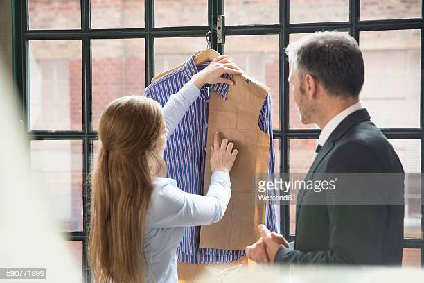 Young seamstress showing customer tailor made shirt