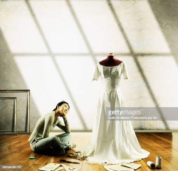 Young seamstress sitting on the floor looking at a wedding gown on a mannequin