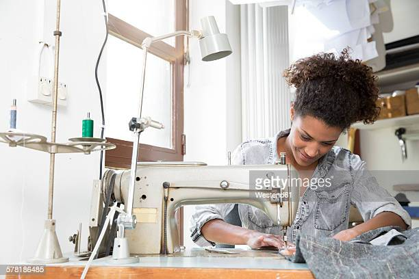 young seamstress with sewing machine in manufacturer's workshop - sewing machine stock pictures, royalty-free photos & images