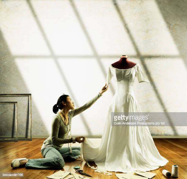 Young seamstress working on a wedding gown on a mannequin