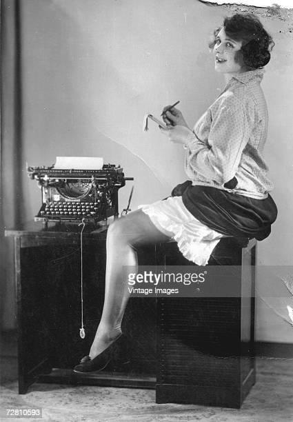 A young secretary holds a notepad as she sits astride a typewriting desk with her skirt and slip raised high enough to see the suspender clips on her...