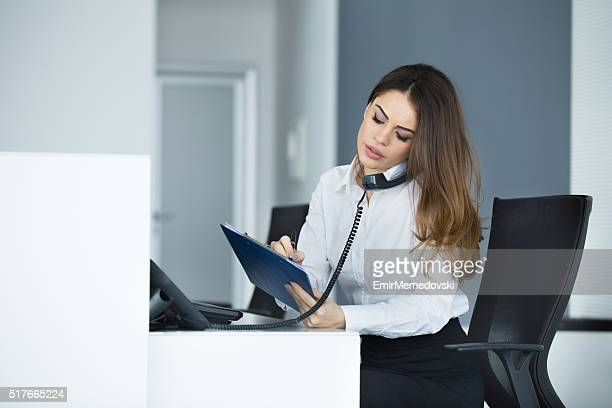 Young secretary talking on the phone and taking notes.