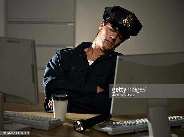 Young security guard sleeping by computers in office