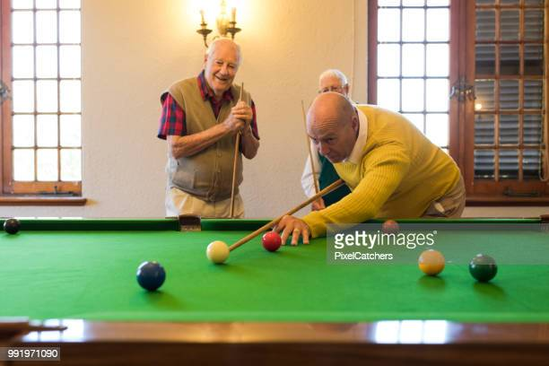 young seniorman playing snooker confident in getting this shot! - old men playing pool stock pictures, royalty-free photos & images