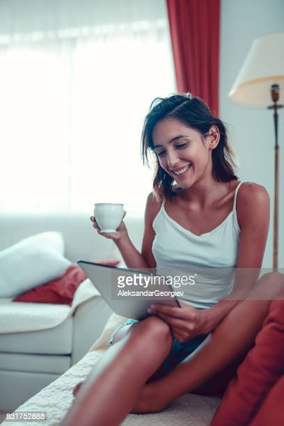 young sensual female drinking coffee and surfing the net on digital tablet in the morning - aleksandar georgiev stock photos and pictures