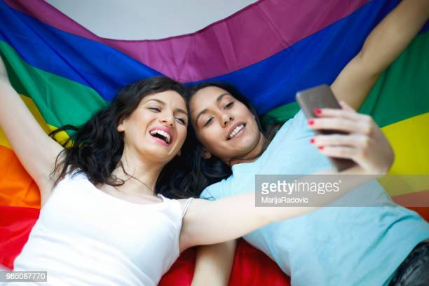 Young sensual lesbian couple lying on lgbt flag and make selfie